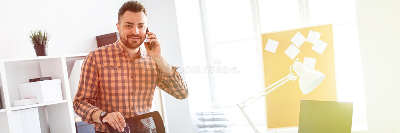 Un hombre se coloca en la oficina cerca de un escritorio del ordenador, pone su mano en la parte de atrás de la silla y habla en  fotografía de archivo libre de regalías