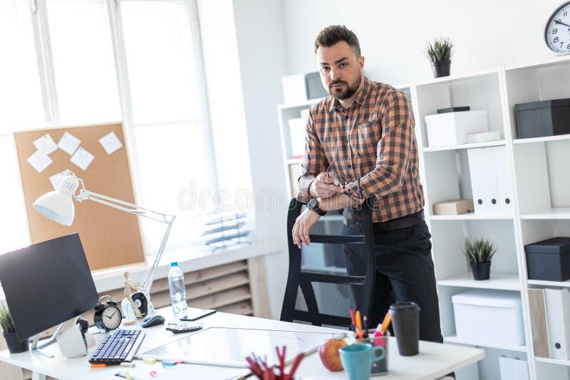 Un hombre se coloca en la oficina cerca de un escritorio del ordenador y pone sus manos en la parte de atrás de la silla imagenes de archivo