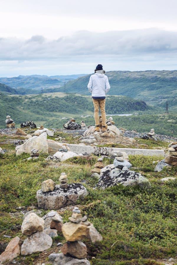 Un hombre se coloca en una colina entre las piedras foto de archivo libre de regalías