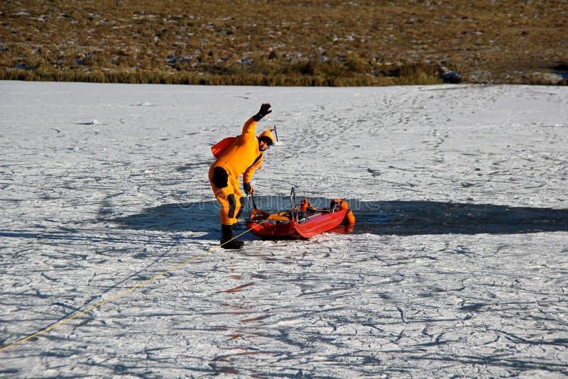 Un hombre se está ahogando en agua helada Un hombre en un traje especial se está ahogando en un lago congelado fotos de archivo