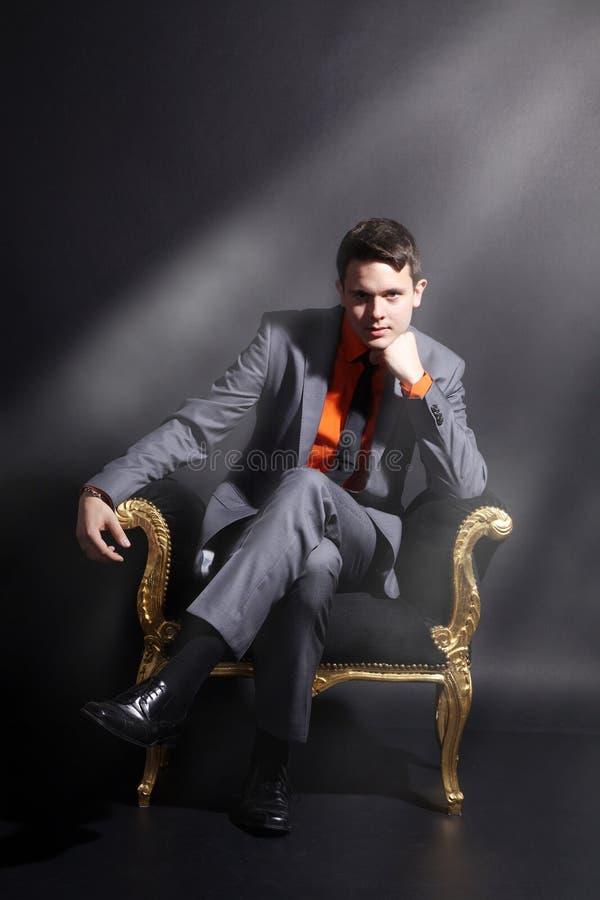 Un hombre se está sentando en una silla fotografía de archivo libre de regalías