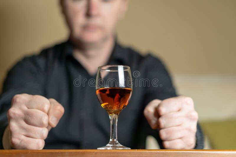 Un hombre se sienta delante de un vidrio de brandy Hombre desenfocado imagen de archivo