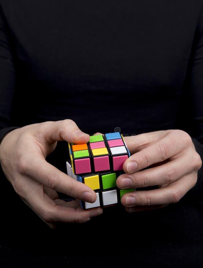 Un hombre se vistió en el negro que sostenía un cubo multicolor fotografía de archivo libre de regalías