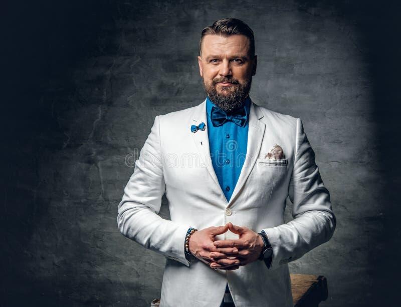 Un hombre se vistió en una camisa azul, una chaqueta blanca y una corbata de lazo foto de archivo libre de regalías