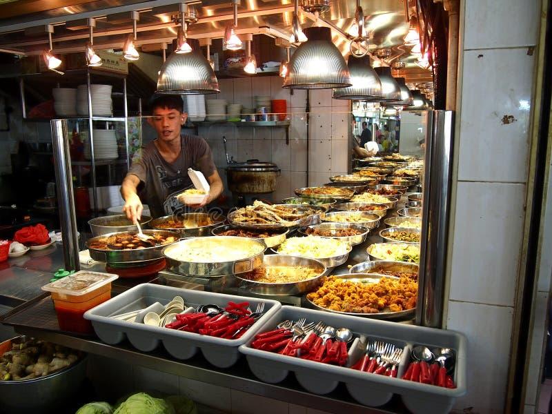 Un hombre sirve la comida para un cliente en un vendedor ambulante en la ciudad de Tampines en Singapur foto de archivo
