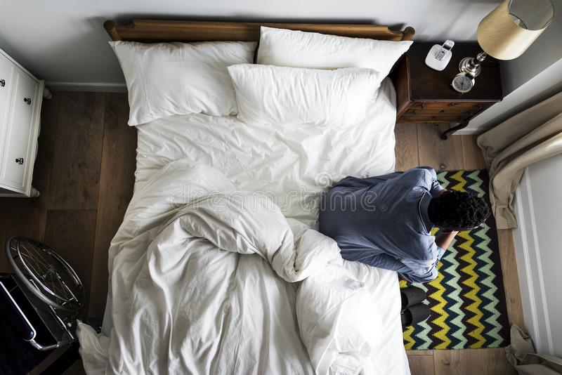Un hombre solo africano que se sienta solamente en la cama fotos de archivo libres de regalías