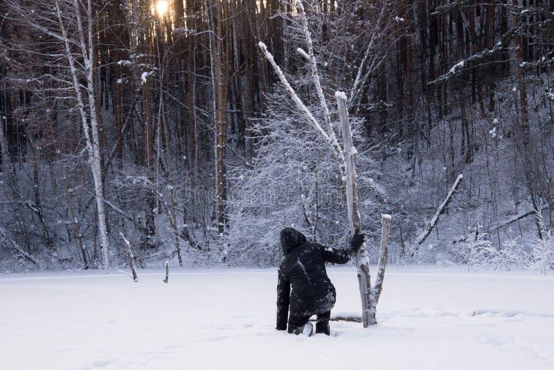Un hombre solo camina en la nieve Silueta dramática de un hombre que camina en un claro nevoso en el bosque frío imagenes de archivo