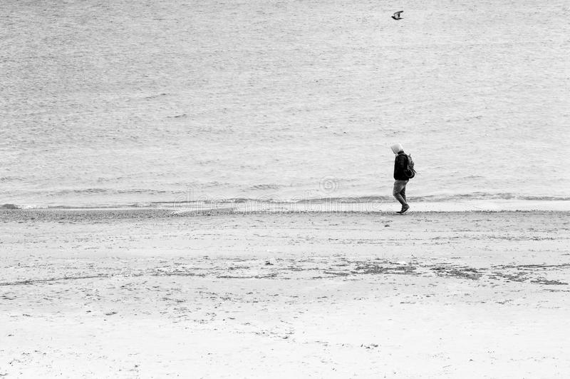 Un hombre solo camina a lo largo de la costa fotos de archivo libres de regalías