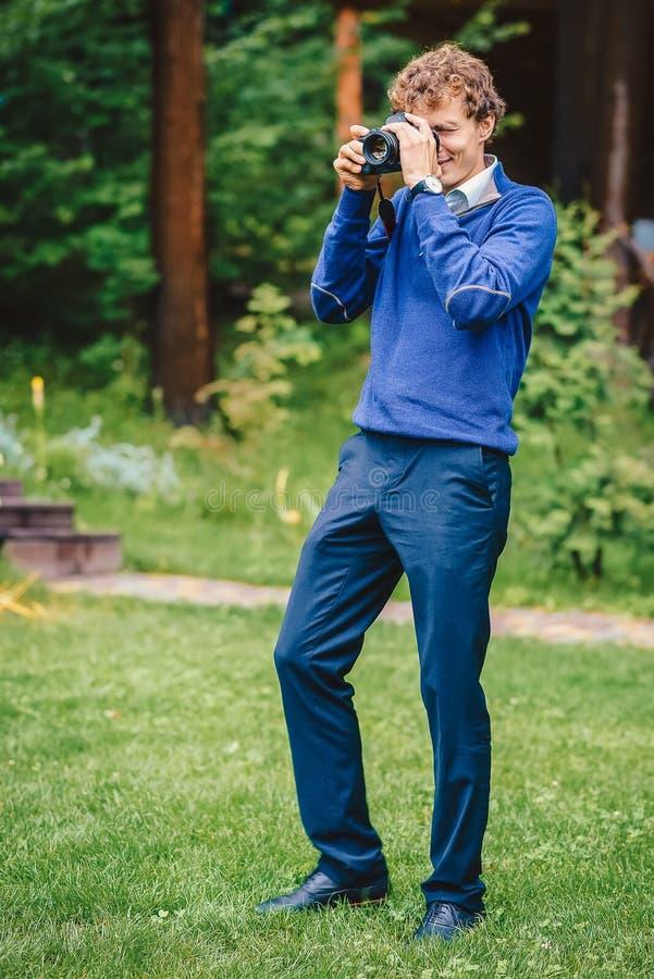 Un hombre sonriente con una cámara Un fotógrafo toma imágenes al aire libre Retrato del primer del fotógrafo en la acción fotos de archivo libres de regalías