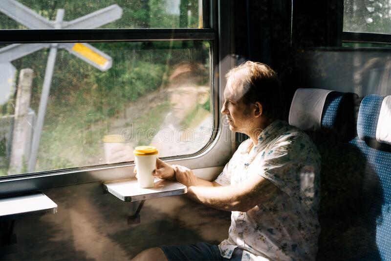 Un hombre sonriente en un tren suburbano mirando por la ventana del tren imagen de archivo libre de regalías