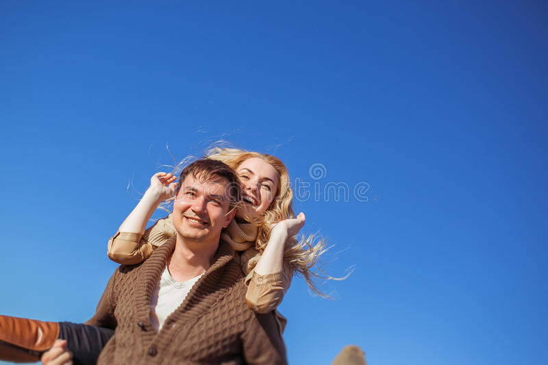 Un hombre sonriente está reteniendo a una mujer de risa en el suyo fotos de archivo