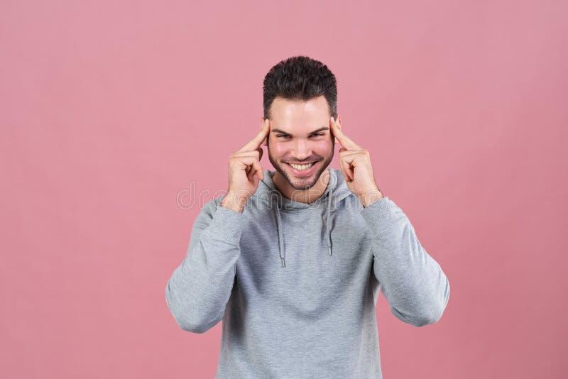 Un hombre sonriente feliz presiona sus fingeres a sus templos en un intento por concentrar y sonríe extensamente El concepto de i imagen de archivo libre de regalías