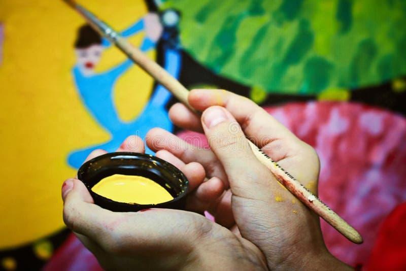 Un hombre sostiene cepillos y la pintura en sus manos y dibuja imagen de archivo