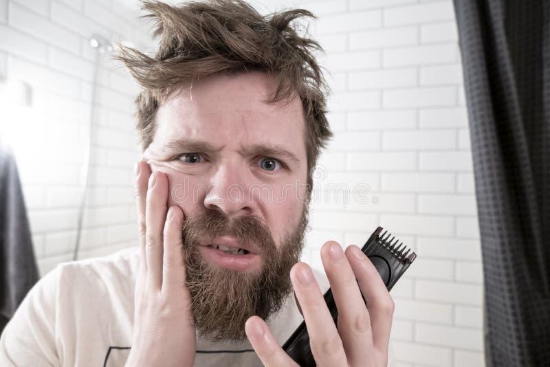 Un hombre sostiene un condensador de ajuste en sus manos que miran su reflexión en el espejo y es horrorizado por su peinado y ba foto de archivo libre de regalías