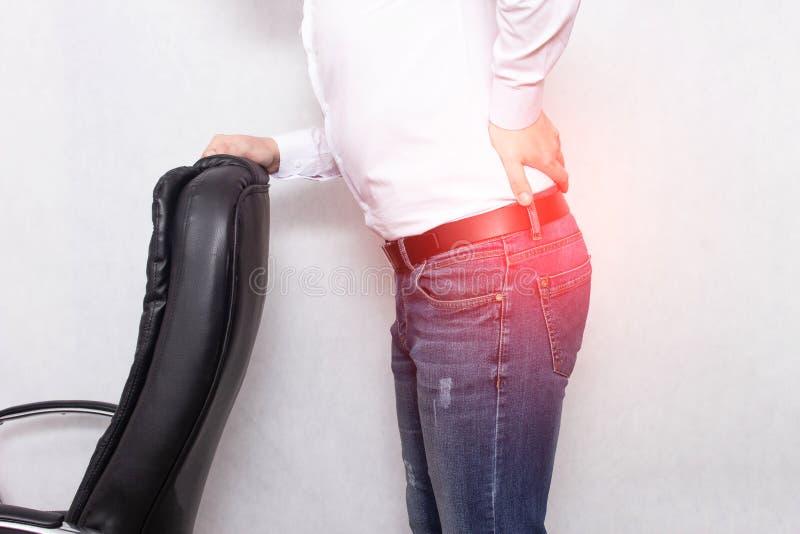 Un hombre sostiene el suyo que refrena un concepto de la silla de la oficina de dolor de espalda, de nervio pellizcado y de síndr fotografía de archivo