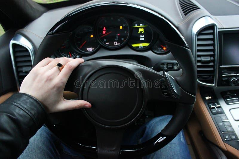 Un hombre sostiene el volante de un coche de lujo fotos de archivo libres de regalías