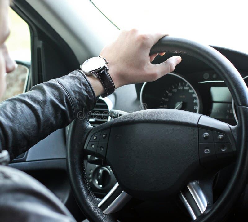 Un hombre sostiene el volante de un coche de lujo fotos de archivo