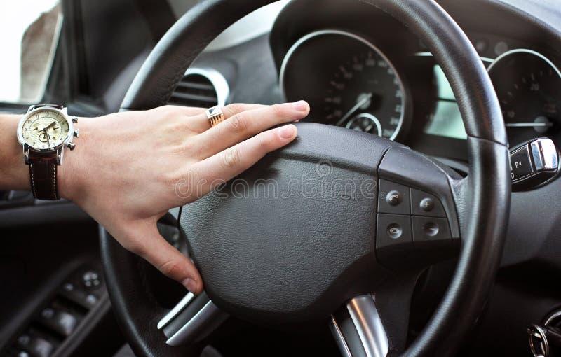 Un hombre sostiene el volante de un coche de lujo imágenes de archivo libres de regalías