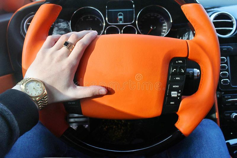 Un hombre sostiene el volante de un coche de lujo Reloj de oro y un anillo en su mano fotos de archivo libres de regalías