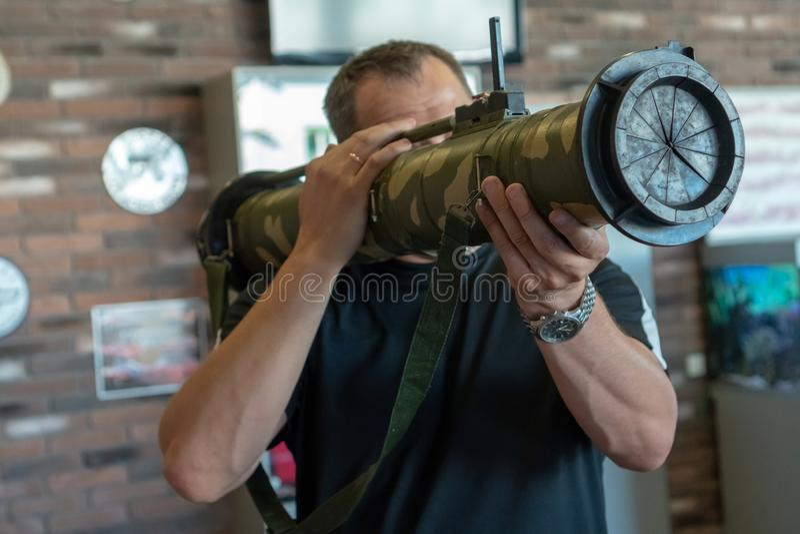 Un hombre sostiene en sus manos una granada del asalto del lanzacohetes contra una pared de ladrillo marrón imagen de archivo