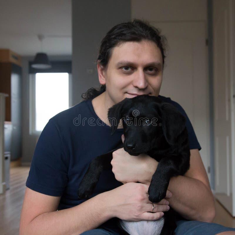 Un hombre sostiene un perrito del labrador retriever foto de archivo