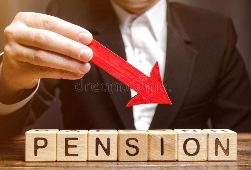 Un hombre sostiene una flecha abajo sobre bloques de madera con la pensión de la palabra Pagos de la pensión de la caída/de la re imagenes de archivo