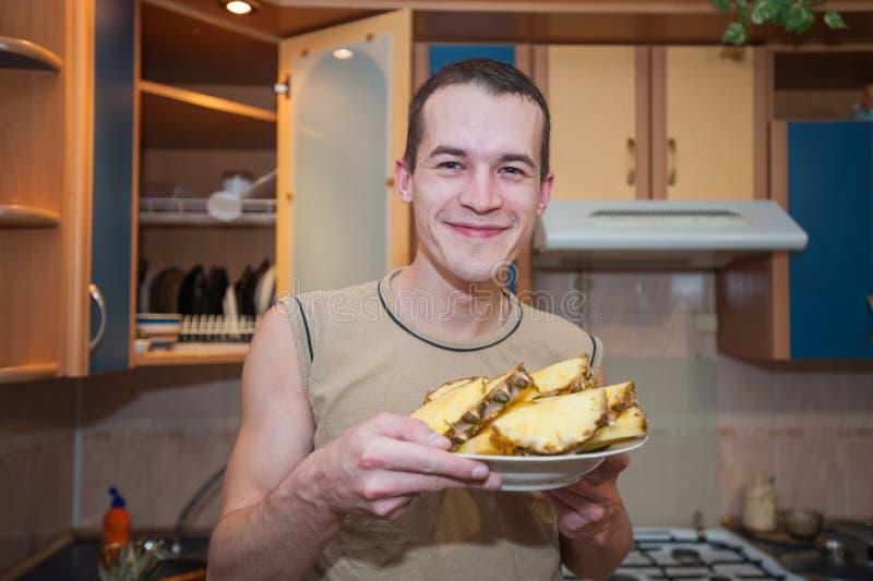 Un hombre sostiene una placa de piñas, piña de los cortes en la cocina y comió foto de archivo libre de regalías