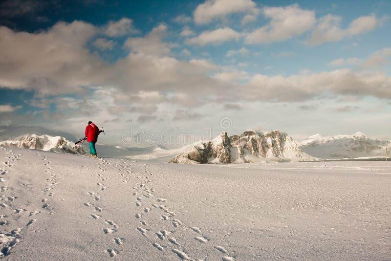 Un hombre sube en una cuesta de la nieve foto de archivo libre de regalías