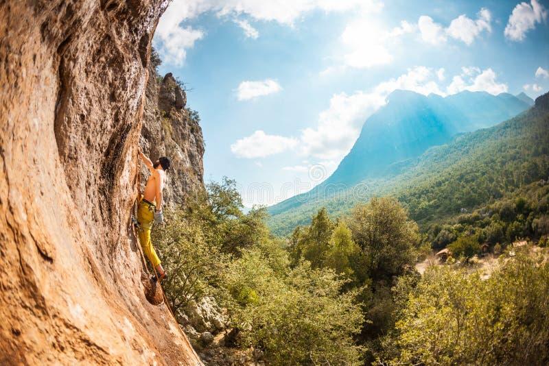Un hombre sube una roca imagen de archivo libre de regalías