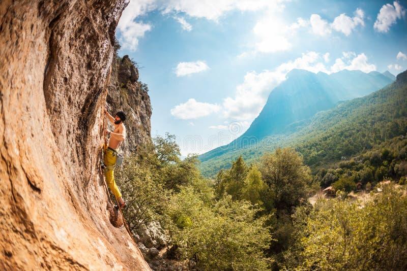 Un hombre sube una roca imágenes de archivo libres de regalías