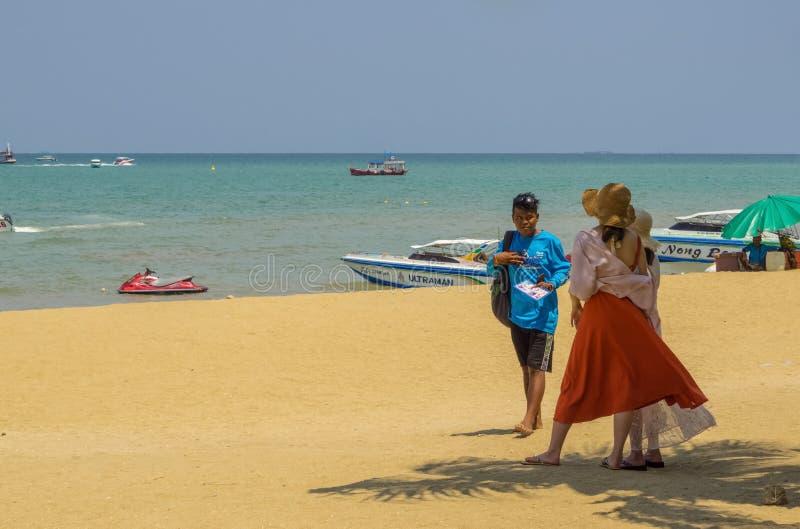 Un hombre tailandés ofrece a dos la mujer china joven un viaje al und Koh Sak de Koh Larn de las islas foto de archivo libre de regalías