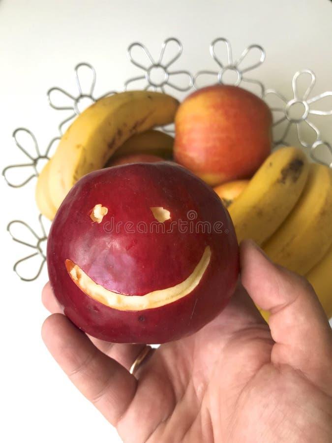 Un hombre toma una manzana roja con un emoticon tallado de un plato Hay una cesta de fruta en el fondo Varias manzanas y plátanos imagen de archivo