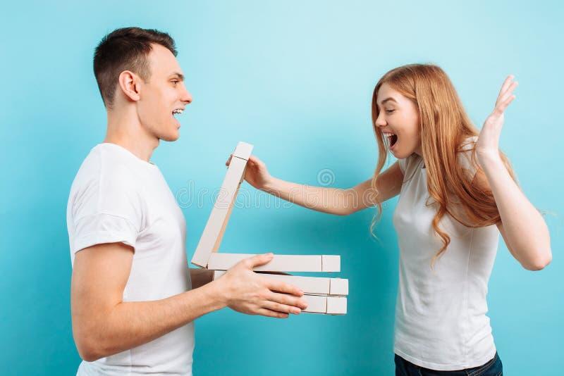Un hombre trajo las cajas de pizza italiana a una mujer que se preparaba para mirar películas en un fondo azul foto de archivo libre de regalías