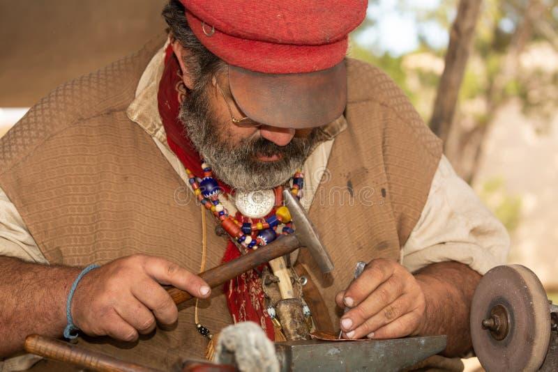 Un hombre vestido como forjador de cobre del 1800's a?ade el detalle a un peque?o pedazo de trabajo con un martillo y una lezna imagen de archivo