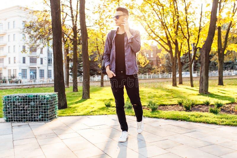 Un hombre un hombre vestido en la ropa elegante, escuchando la música a través de los auriculares inalámbricos y caminando en el  fotos de archivo libres de regalías