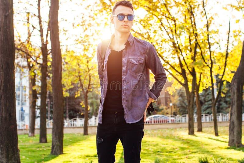 Un hombre vestido en la ropa elegante, gafas de sol, paseos en el parque, foto de archivo