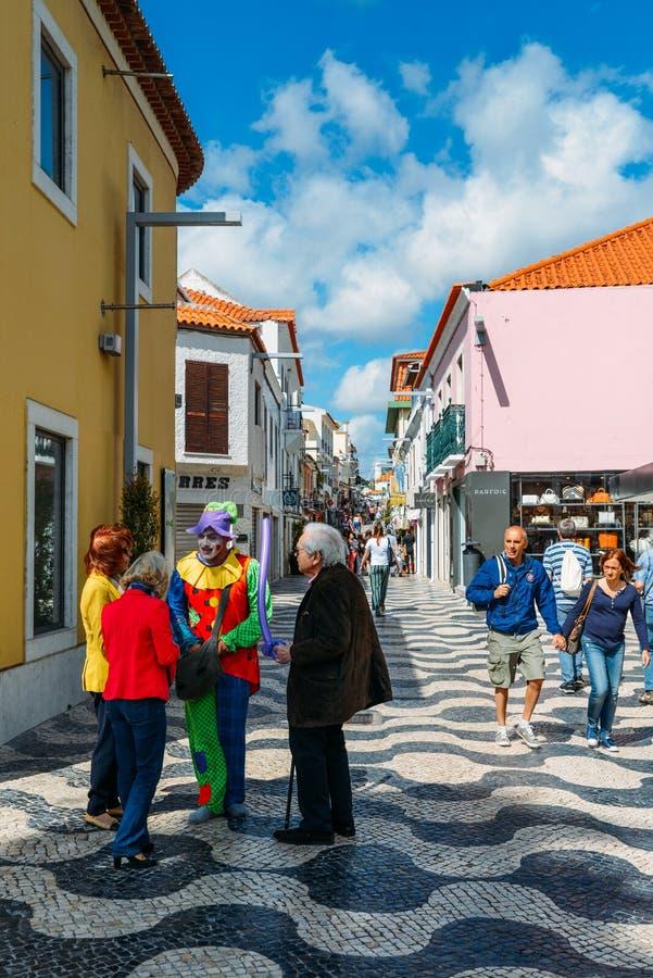 Un hombre vestido encima como de payaso habla a los locals en una calle comercial ocupada en el corazón de Cascais, Portugal imagen de archivo