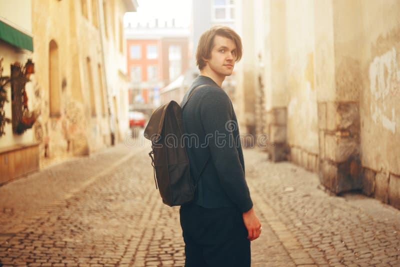Un hombre viaja en Europa Un hombre sonríe, camina a través de las calles de la ciudad vieja, con una cartera fotos de archivo