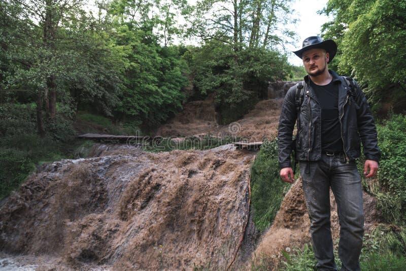 Un hombre, un viajero en una chaqueta de cuero y un sombrero de vaquero Cascada lleno-que fluye grande con agua sucia, un viaje,  imagen de archivo