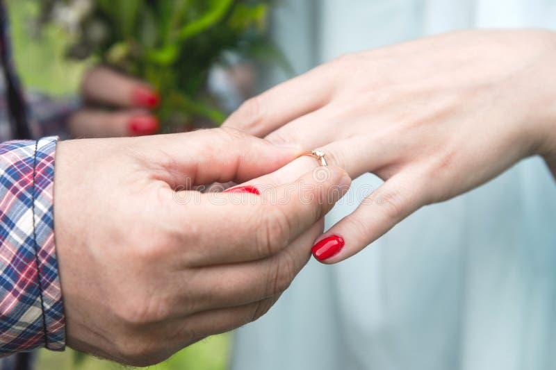 Un hombre viste un anillo de compromiso para una muchacha en el dedo anular de su mano izquierda fotos de archivo libres de regalías