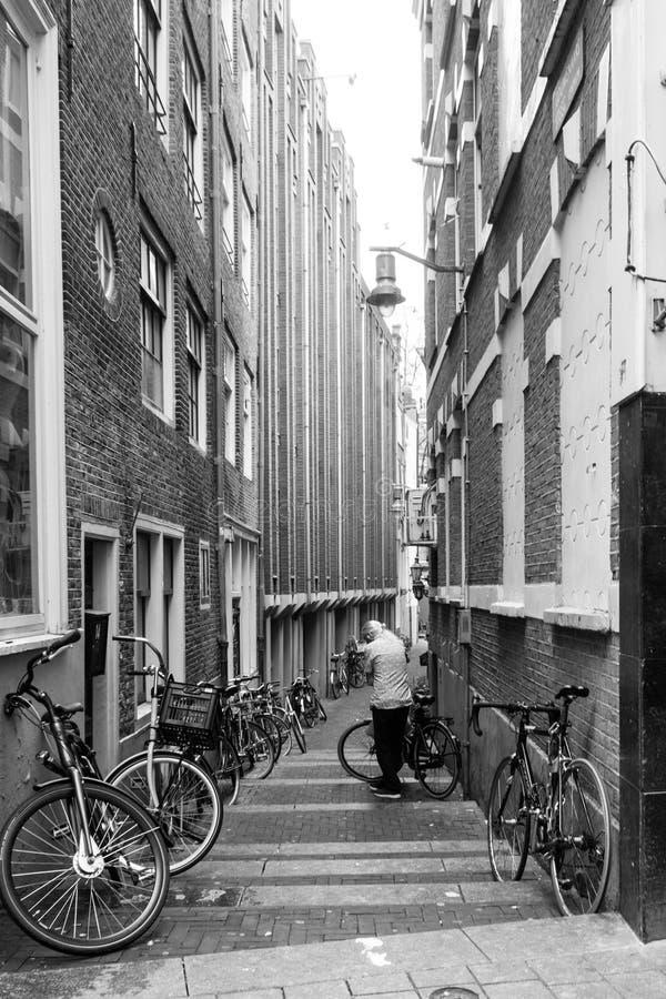 Un hombre y su bicicleta en un pasillo de Amsterdam foto de archivo
