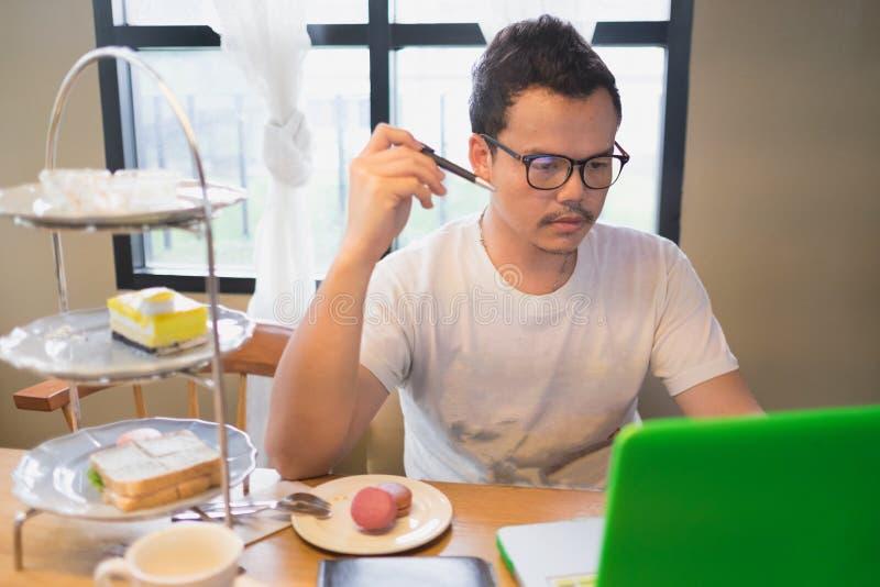 Un hombre y su ordenador con la cara de pensamiento en el tiempo del té imagenes de archivo