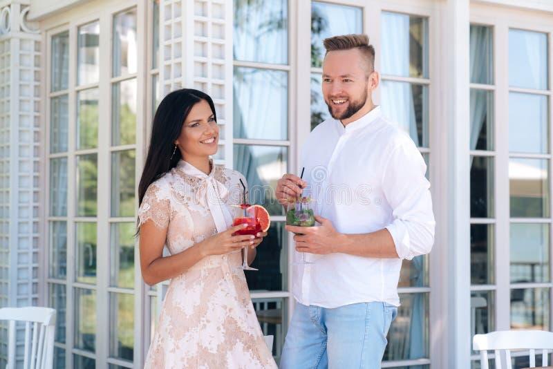 Un hombre y una mujer atractivos vinieron a un acontecimiento Beben los cócteles en un partido, se divierten, sonrisa, pasan tiem imagen de archivo libre de regalías