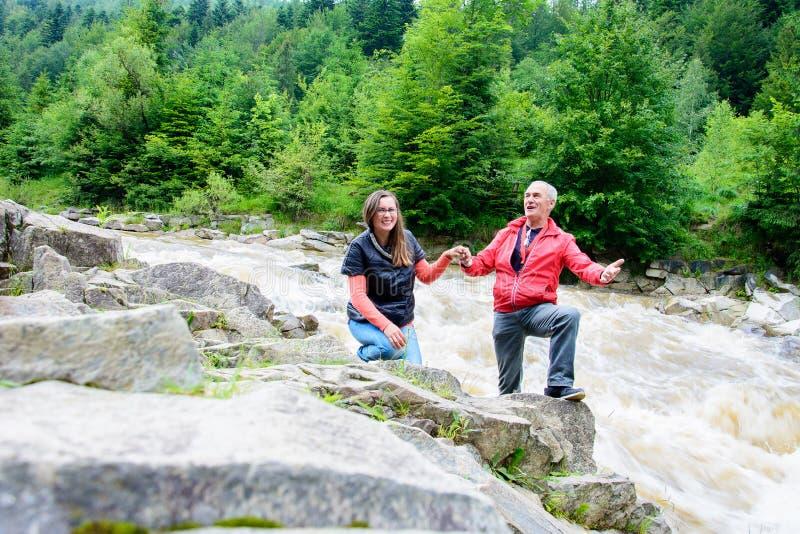 Un hombre y una mujer cantan en los Cárpatos en el fondo del río imagen de archivo