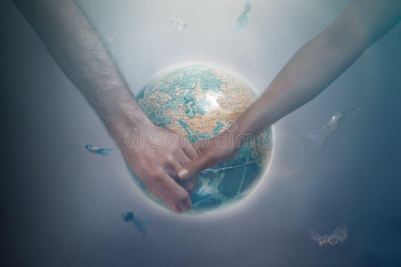 Un hombre y una mujer de diversas razas que celebran las manos en el fondo del globo de la tierra del planeta r imagenes de archivo