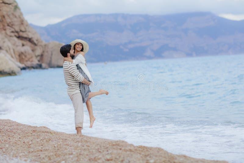 Un hombre y una mujer en amor que gozan junto cerca del mar, corriendo por la playa, riendo, bes?ndose fotografía de archivo