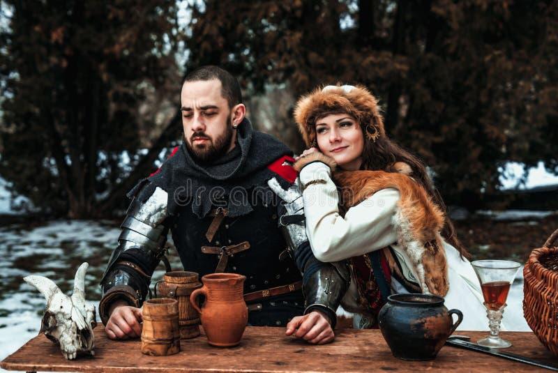 Un hombre y una mujer en trajes históricos se están sentando en una tabla foto de archivo libre de regalías