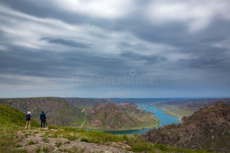 Un hombre y una mujer están caminando en naturaleza El río de Ili imagen de archivo