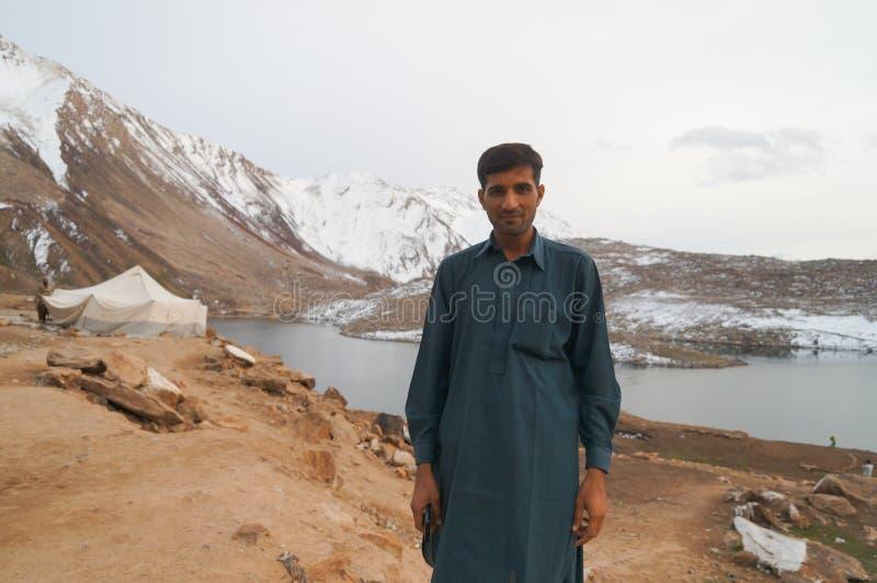Un hombre y una tienda para la gente local en el lago cerca de Babusar pasan, fotos de archivo libres de regalías