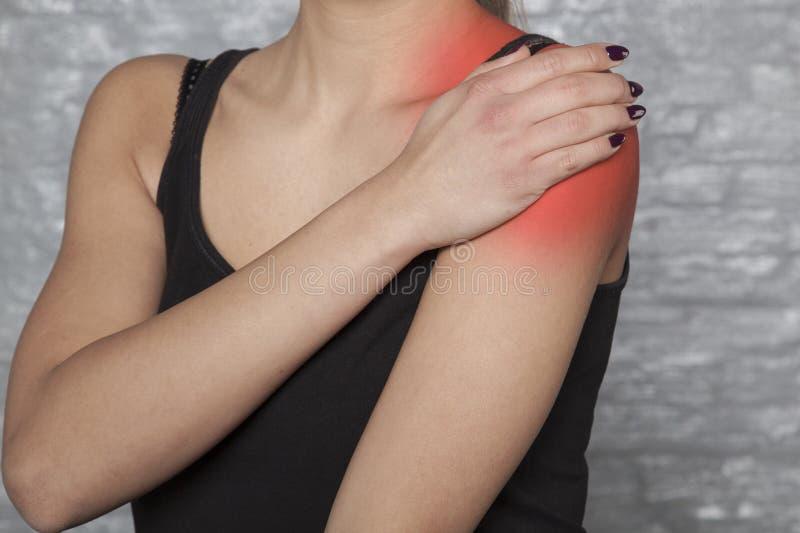 Un hombro herido, daños una mujer foto de archivo